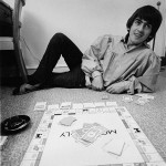 George Harrison playing monopoly during the Beatles tour of the USA. at rented Bel Air home with Jackie de Shannon (out of shot) August 1964
