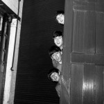 The Beatles peering out from behind a door. before the groups appearence at Sunday Night at the London Palladium, 13 October 1963