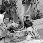 relax on sun loungers at their rented house in Bel Air, Los Angeles, 24 August 1964 during a break in the Beatles' first concert tour of America